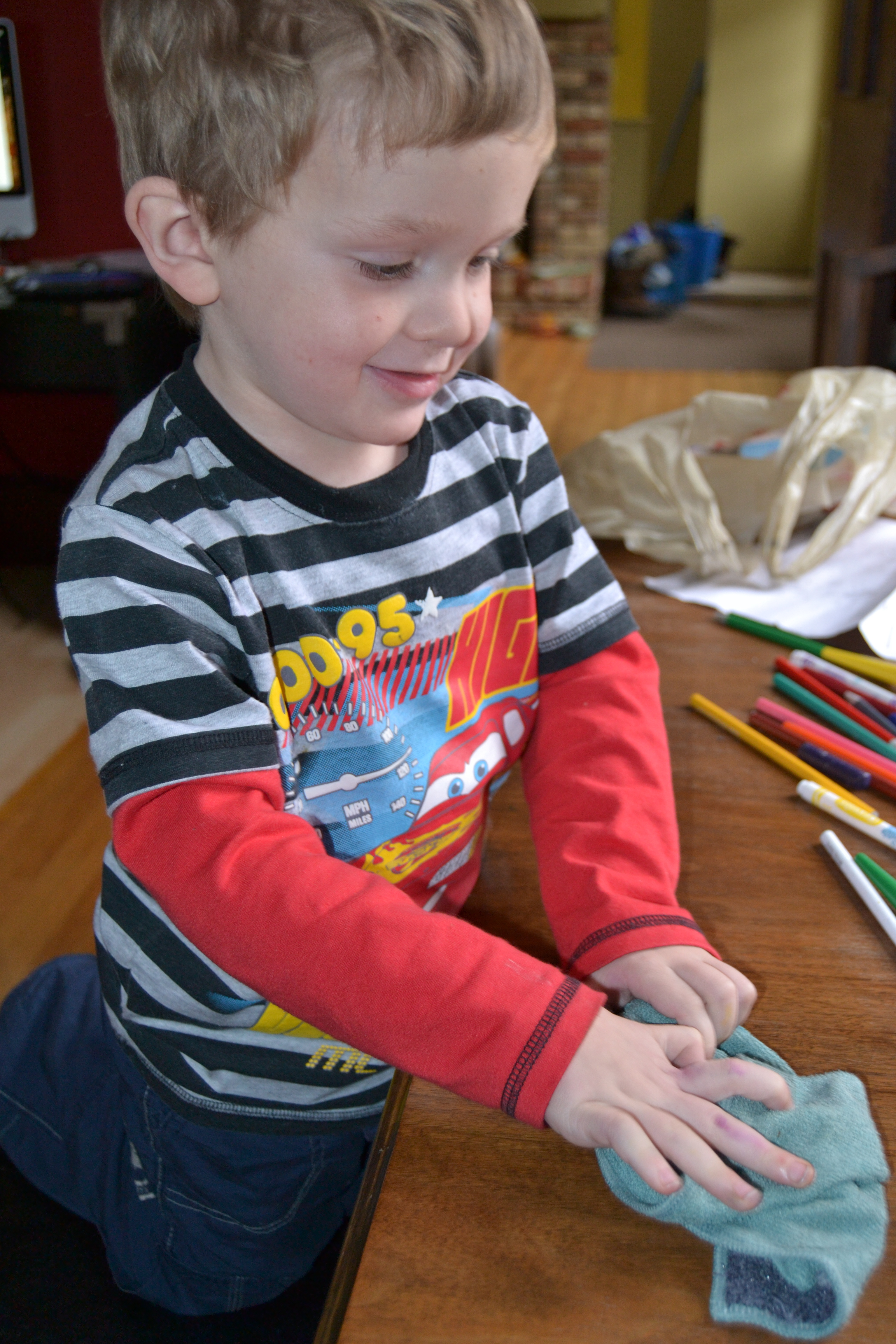 Zander using the kitchen e-cloth to wipe up marker and paint from the table
